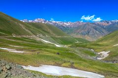 Song Kul Lake 04. Car Road Toward Song Kul Lake with Snow Capped Mountains Landscape royalty free stock images