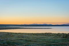 Song Kul lake in sunrise, Kyrgyzstan. Song Kul lake in mist in early morning light, Kyrgyzstan Royalty Free Stock Images