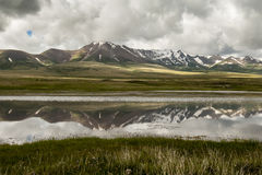 Song Kul lake reflection. Mountain reflection at Song Kul lake in Kyrgyzstan stock photo