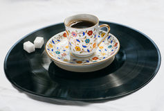 Song of a morning concept. Retro sound vinyl plate and cup of coffee with sugar. Stock Photos