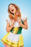 Song about pretzels. Young Oktoberfest woman wearing a traditional Bavarian dress dirndl holding two pretzels and singing on blue background royalty free stock image