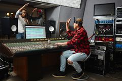 Song recording. Sound operator showing okay gesture to young musicians while recording their songs in audio studio Stock Image