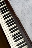 Song sheet music on wooden upright piano with white and black k. Sheet music songbook on brown wooden piano with white and black keys royalty free stock photography