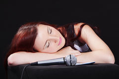 Song to you. Young girl with microphone is composing some romantic song. Looks like she is tired and trying to sleep Royalty Free Stock Photography
