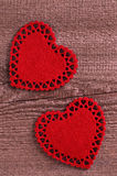 Song for Valentine's day. Two red hearts cut from soft tissue lying on old wooden boards Stock Photos