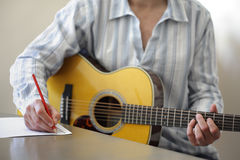 Song writing on acoustic guitar. Guitarist musician writing a song on his guitar Stock Photography