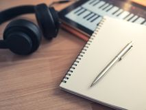 Song Writing. Music Creation Tools, Headphone, Notebook, Electronic Tablet and Pen on Wooden Background stock photos