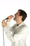 A song for you. Young man singing softly with his eyes closed to a microphone isolated over white backround Stock Photo