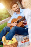 This song is for you. Happy young men is playing guitar for woman. He is looking at her with love and smiling. Couple is sitting on blanket in park Stock Photography