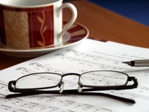 Songbook and glasses. Place of employment of a music teacher. Glasses on the songbook and  cup of  coffee in the background Royalty Free Stock Photography