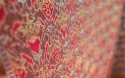 Songket with blurry effect background. Songket is a fabric that belongs to the brocade family of textiles of the Malay world It is hand-woven in silk or cotton Stock Image