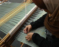 Songket Making. Songket is a fabric that belongs to the brocade family of textiles of Indonesia, Malaysia and Brunei. It is hand-woven in silk or cotton, and Stock Photo