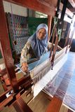 Songket craftswoman. The songket technique itself involves the insertion of decorative threads in between the wefts as they are woven into the warp, which is royalty free stock image