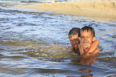 SONGKHLA, TAILANDIA - 24 DE JULIO: Los dos muchachos no identificados juegan en la agua de mar en julio 24,2017 en el nombre del  Foto de archivo libre de regalías