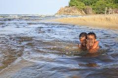 SONGKHLA THAILAND - JULI 24: Oidentifierade två pojkar spelar i havsvatten på Juli 24,2017 på namnet för Kaoseng slumkvarter` s,  Arkivbild