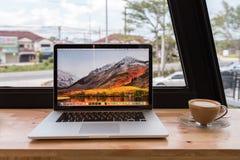 SONGKHLA THAILAND - September 23, 2018: Apple Macbook pro-dator med kaffekoppen på trätabellen som skapas av Apple Inc royaltyfria bilder