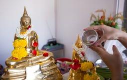 Songkran天,泰国文化概念,手妇女用途对金黄菩萨雕象的裂片打击 免版税库存照片