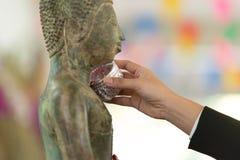 Songkran节日在泰国-倾吐与茉莉花和玫瑰的人水对菩萨雕象 免版税库存照片