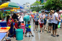 Songkran battle. Bangkok, Thailand, 14 April 2015. Groups of partygoers splahs water at each other using water guns, buckets and hoses. The annual Songkran water stock image
