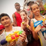 Songkran in Chiang Mai, Thailand. On the 15th of April 2014.nA young woman is throwing water at the camera using a water gun Stock Photo