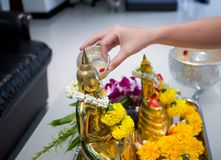 Songkran day, Thai culture concept, Hand woman use the sliver blow to golden buddha statue. Festival of thailand Royalty Free Stock Photos