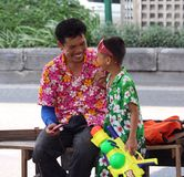 Songkran 2017 father and son share some fun in Bangkok. In shirts and gear father and son enjoy the moment Stock Photos