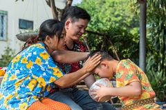 Songkran Festival bathe with respect to parents. Ang Thong, Thailand - April 13, 2018 : Unidentified Asian young bathe with respect to parents by water have a royalty free stock photo