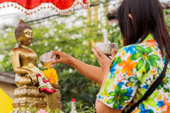 Songkran Festival. NAKHON SRI THAMMARAT, THAILAND - APRIL, 12: Unidentified Thai woman celebrate Songkran Festival by pouring water to Buddha statue on April 12 Stock Photos