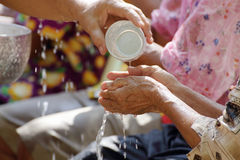 Songkran festival. Pour water on the hands of revered elders and ask for blessing in Songkran festival Stock Photo