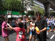 Songkran festival at Silom Road in Bangkok on April 2012. Usually non-Thai people is not targeted in this water battle, but there is always an exception. I Stock Image