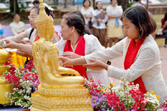 Songkran Festival. Thai women pouring water to gold Buddha statue in Songkran Festival - water festival - 2015 at temple in Ayutthaya, Thailand Stock Image