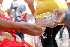 Songkran Festival, Thailand. Close-up Thai people pouring water bathing on hand of monk in Songkran Festival, Thailand Stock Image
