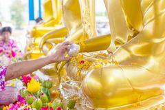 Songkran festival in Thailand, Hand woman use the water pouring to golden buddha statue. Traditions that have long inherited Stock Photo