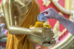 Songkran festival in Thailand, Hands man use the water pouring t. O golden buddha Stock Photo