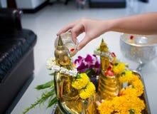 Songkran-Tag, thailändisches Kulturkonzept, Handfrauengebrauch der Splitterschlag zu goldener Buddha-Statue lizenzfreie stockfotos