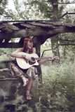 From songs to live cheerfully!. The cheerful girl with a guitar sits on the brink of a well Stock Photo