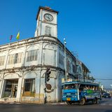 A songthaew, local bus passing by the Promthep Clock Tower. PHUKET TOWN, THAILAND - March 3: A songthaew, local bus passing by the Promthep Clock Tower on March Royalty Free Stock Images