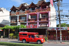 Songthaew or Red Car Taxi in Thailand. Songthaew or Red Car Taxi on Huay Keow Road in Chiang Mai, Thailand. Traditional residential/commercial building in stock photos