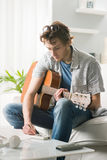 Songwriter composing a song. Young man playing guitar and composing a song sitting on sofa Stock Photos