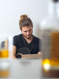 Songwriter concentrating on writing. Photo of a male songwriter with acoustic guitar taken between a blurred whisky bottle and rocks glass Stock Photo