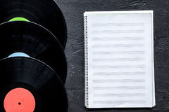 Songwriter or dj work place with notebook and vynil record on black background top view mockup. Songwriter or dj work place with notebook and vynil record on royalty free stock photos