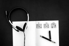 Songwriter or dj work place with notes and headphones on black background top view. Songwriter or dj work place with notes and headphones on desk black royalty free stock photos