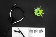 Songwriter or dj work place with notes and headphones on black background top view. Songwriter or dj work place with notes and headphones on desk black stock image