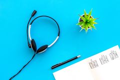 Songwriter or dj work place with notes and headphones on blue background top view. Songwriter or dj work place with notes and headphones on desk blue background stock photography