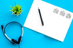Songwriter or dj work place with notes and headphones on blue background top view mock up. Songwriter or dj work place with notes and headphones on desk blue royalty free stock images