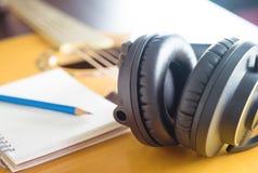 Songwriter materiaal met hoofdtelefoonnotitieboekje op gitaar stock afbeeldingen