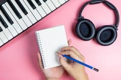 Songwriter schrijft zijn nieuwe muziek op leeg notitieboekje stock fotografie