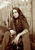 Songwriter sepia. A beautiful country singer with a dobro guitar, thinking about her songwriting. Little bit of film grain Royalty Free Stock Photo