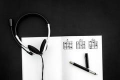 Songwriter of van DJ het werkplaats met nota's en hoofdtelefoons op zwarte hoogste mening als achtergrond royalty-vrije stock foto's