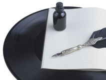 Songwriting. White notebook, black old pen and ink laying over a vinyl record Stock Image